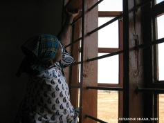 Woman standing at window in schoolhouse in Isandula, Tanzania. Photo, Suzanne Skaar. 2015.