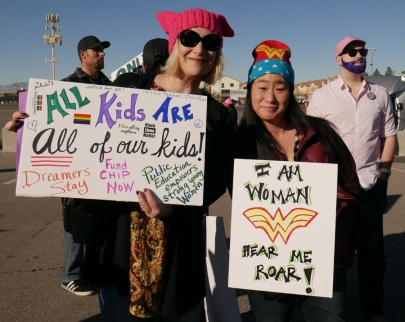 "Attendees holding signs at 2018 Las Vegas Women's Rally: ""All Kids are all of our kids"" and ""I am Woman, Hear Me Roar."""