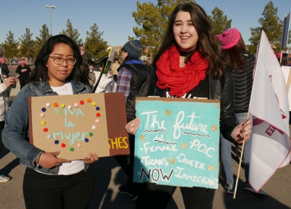 "Attendees holding signs at 2018 Las Vegas Women's Rally: ""Viva la mujer"" and ""The Future is Femme, POC, Trans, Queer, Immigrant, Now""."