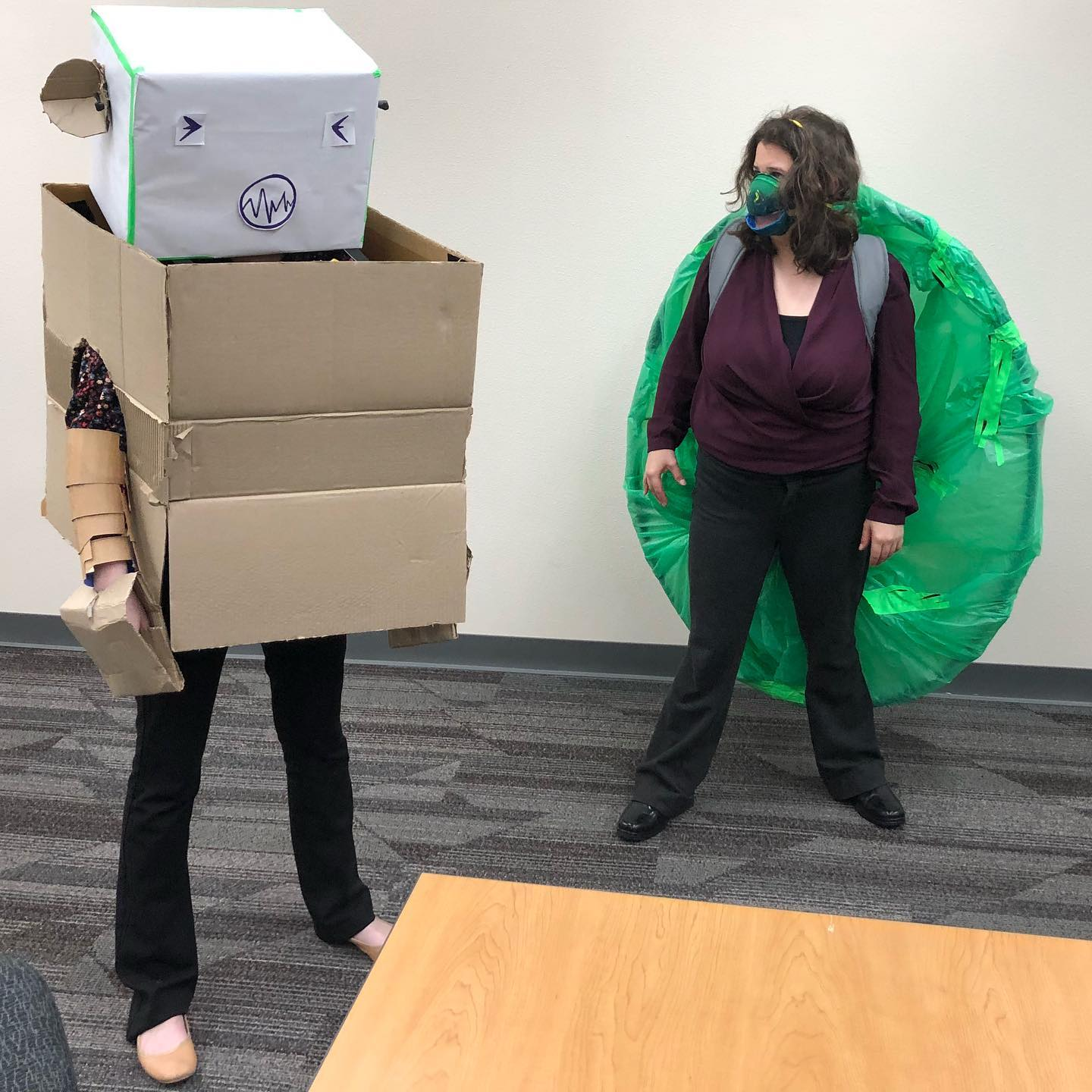 Actors standing in handmade giant cardboard box robot and giant turtle costumes.