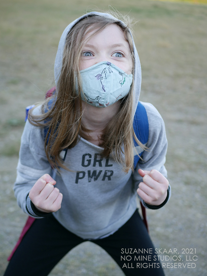 """Child wearing gray hoodie which reads """"GRL PWR"""" (Girl Power) crouched, fists raised, and eyes wide."""
